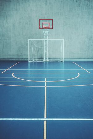 Photo for Front view of the court in the gym hall; indoors modern contemporary office stadium with a basketball basket and hoop, football goal, colored marking on the floor, a concrete wall in the background - Royalty Free Image