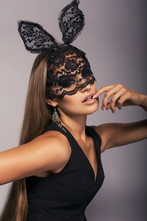 Photo for fashion studio portrait of sexy woman with long straight hair in elegant black dress in lace bunny mask - Royalty Free Image