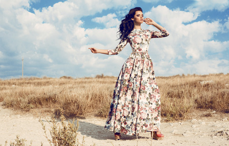 Foto de fashion outdoor photo of beautiful woman with dark curly hair in luxurious floral dress posing in summer field - Imagen libre de derechos