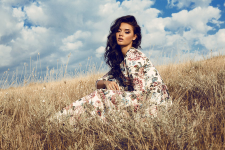 Foto de fashion outdoor photo of beautiful woman with dark hair in elegant floral dress posing in summer field - Imagen libre de derechos