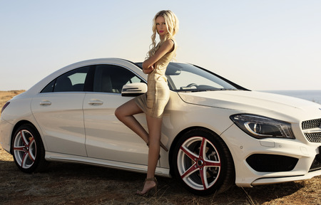 fashion outdoor photo of beautiful glamour woman with long blond hair in elegant gold dress posing beside a luxury car