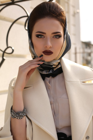 Photo for fashion outdoor photo of beautiful young woman with dark hair and bright makeup,wearing elegant beige coat and silk scarf on head - Royalty Free Image