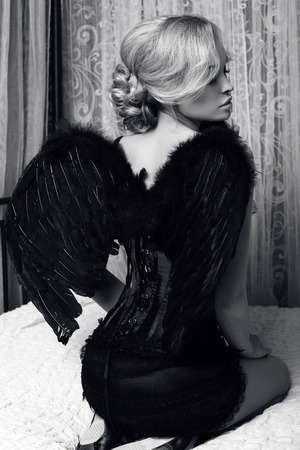 black and white fashion photo of beautiful sexy girl with blond hair in luxurious clothes with black wings