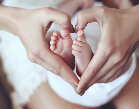 Photo for tender interior photo of cute baby feets in mom hands holding them in heart shape - Royalty Free Image