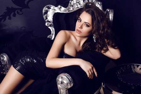 Photo pour fashion photo of gorgeous woman with long dark hair in elegant dress posing in luxurious interior - image libre de droit
