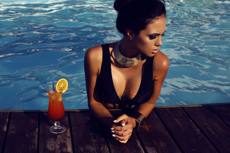 fashion outdoor photo of beautiful sensual woman with long dark hair in elegant black swimsuit relaxing in swimming pool with cocktail