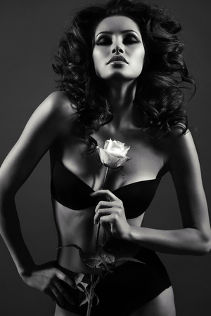 Foto de black and white fashion photo of beautiful sexy woman with luxurious curly hair in elegant lingerie posing in studio,holding rose in hands - Imagen libre de derechos