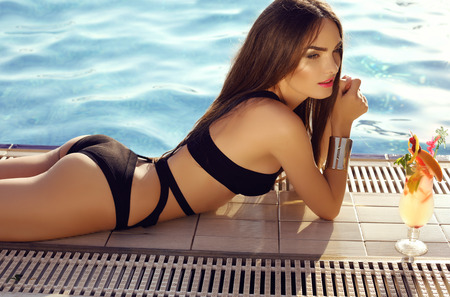 fashion outdoor photo of beautiful sensual woman with dark hair wearing elegant bikini, posing beside swimming pool with cocktail