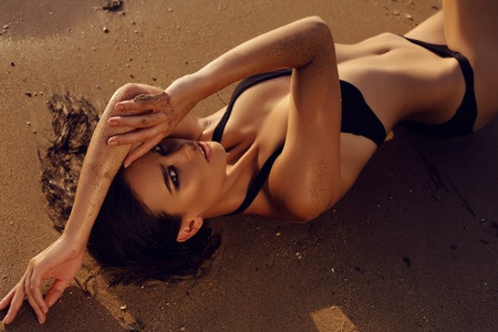 Foto de fashion outdoor photo of beautiful sexy girl with dark hair and tanned skin wears black bikini relaxing on summer beach - Imagen libre de derechos