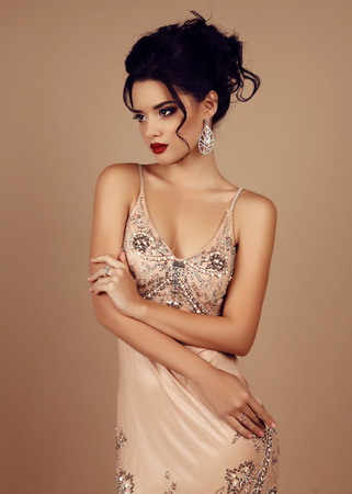 Photo for fashion studio photo of gorgeous woman with dark hair wears luxurious sequin dress and precious bijou - Royalty Free Image