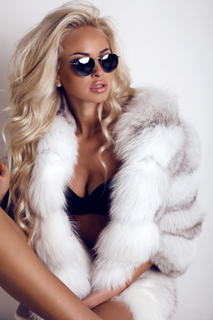 Photo for fashion studio  photo of gorgeous sexy woman with long blond hair wears luxurios fur coat and sunglasses - Royalty Free Image