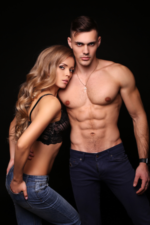 Foto de fashion studio photo of beautiful couple with sportive sexy bodies, gorgeous woman with long blond hair embracing handsome brunette man - Imagen libre de derechos