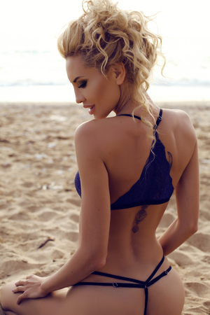 Photo pour fashion outdoor photo of gorgeous sexy woman with blond curly hair in elegant lingerie posing at summer beach - image libre de droit