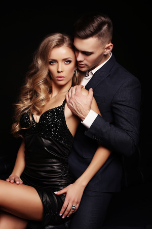 Photo pour fashion studio photo of sexy beautiful couple. gorgeous woman with blond hair and handsome man in elegant clothes - image libre de droit