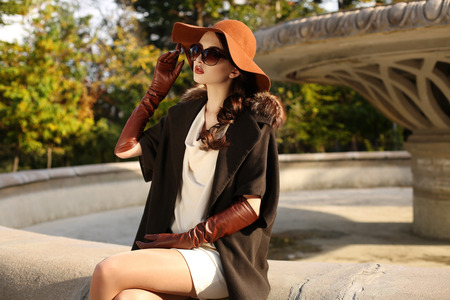 Photo for fashion outdoor photo of gorgeous sensual woman with dark hair in elegant luxurious coat, wool hat and leather gloves, walking by autumn city - Royalty Free Image