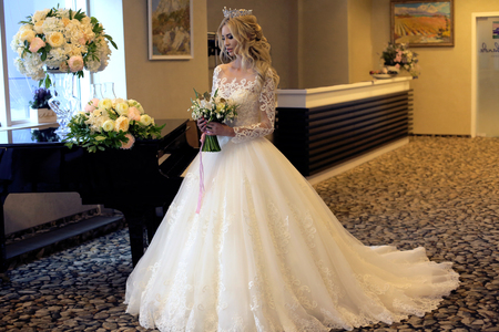 Photo pour fashion interior photo of gorgeous bride with blond hair in luxurious wedding dress posing in decorated room - image libre de droit