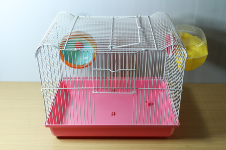 Photo for old and empty white and pink hamster cage on wood desk with hamster wheel and yellow hamster toilet - Royalty Free Image