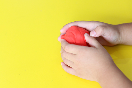 Photo for kid knead red play dough on yellow table - Royalty Free Image