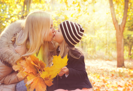Foto de Happy daughter kissing her mother in autumn park and play collects a bouquet of yellow maple leaves. - Imagen libre de derechos