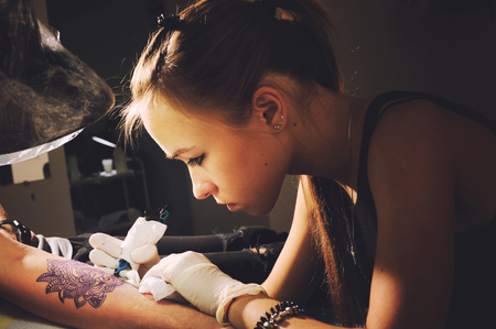Photo pour Portrait of a young cute woman master tattooist makes the tattoo on hand on a purplish blue likeness of a future tattoo, under the lamp light. - image libre de droit
