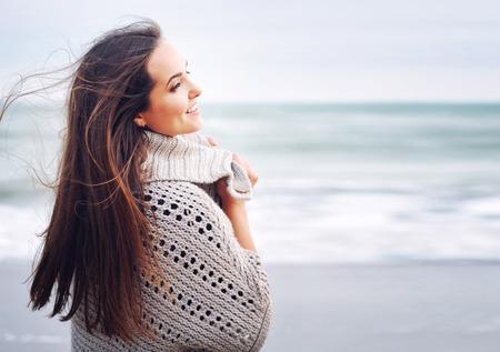 Foto de Young beautiful smiling woman portrait against ocean background, winter outdoor - Imagen libre de derechos