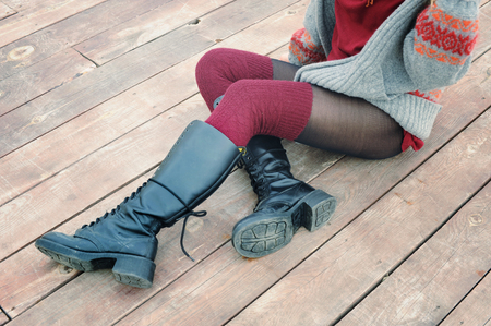 Foto de Female legs dressed in knee high boots and knitted stockings, woman sitting on a wooden planking, winter outdoor - Imagen libre de derechos