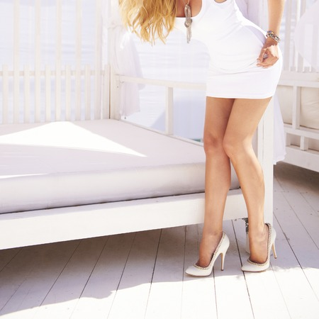 Foto de Sexy female legs in white fashion classical shoes on a heel. - Imagen libre de derechos