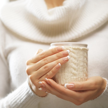 Foto de Woman holds a winter cup close up on light background. Woman hands with elegant french manicure nails design holding a cozy knitted mug. Winter and Christmas time concept. - Imagen libre de derechos