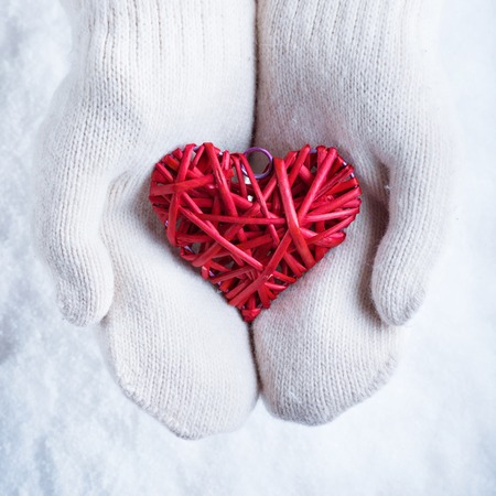 Photo for Female hands in white knitted mittens with a entwined vintage romantic red heart on a snow background. - Royalty Free Image