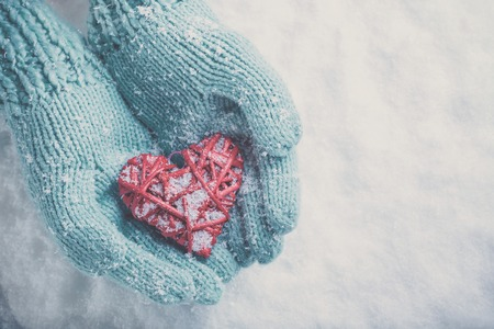 Woman hands in light teal knitted mittens are holding a beautiful glossy red heart in a snow winter background