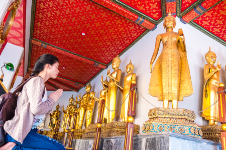 Photo for Asian women tourist backpack is worshiping the image of Buddha in holiday at wat pho Bangkok Thailand. It is a landmark and attraction. - Royalty Free Image