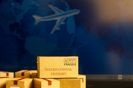 Foto de Small paper boxes on notebook with a plane flies behind. An ideas about transportation, international freight, global shipping, overseas trade, regional, or local forwarding. - Imagen libre de derechos