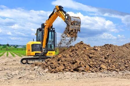 Foto de The modern excavator  performs excavation work on the construction site - Imagen libre de derechos