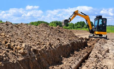 Foto de A modern excavator is performing excavation work on the pipeline repair - Imagen libre de derechos