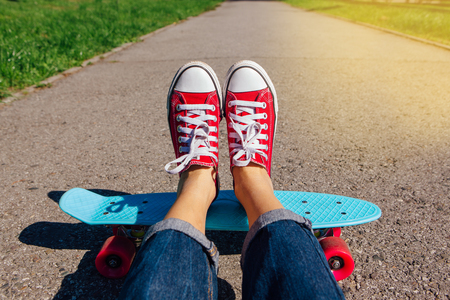 Photo for Close up of feet of a girl in red sneakers rides on blue plastic penny skate board with pink wheels. Urban scene, city life. Sport, fitness lifestyle. - Royalty Free Image