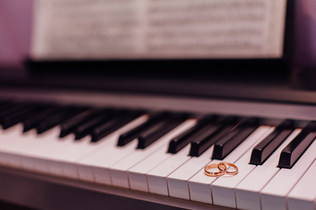 Photo pour Two golden wedding rings laying on the piano keys - image libre de droit