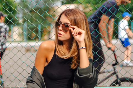 Photo pour Fashion portrait of trendy young woman wearing sunglasses, and bomber jacket sitting next to rabitz in the city. Copy space. - image libre de droit