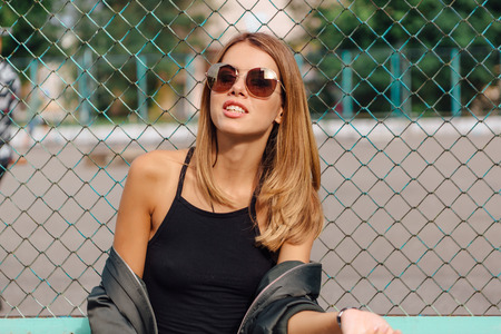 Foto de Fashion portrait of trendy young woman wearing sunglasses, and bomber jacket sitting next to rabitz in the city. Copy space. - Imagen libre de derechos