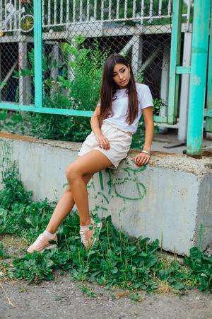 Foto de Portrait of a young brunette swag girl sitting next to rabitz fence. - Imagen libre de derechos