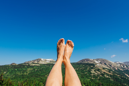 Photo for Female feet up infront of the clear blue sky and mountains - Royalty Free Image