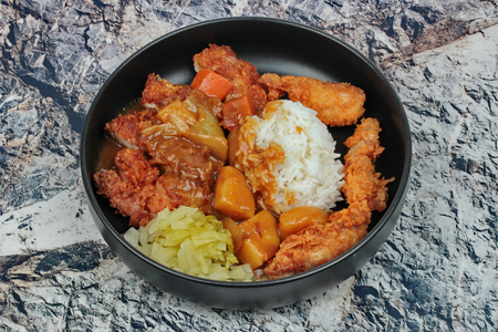 Foto de Rice with deep fried chicken,sliced picklesl topped Japanese yellow curry . - Imagen libre de derechos