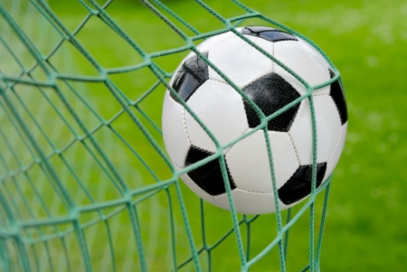 Photo pour Close-up of a soccer ball flying into the net - image libre de droit
