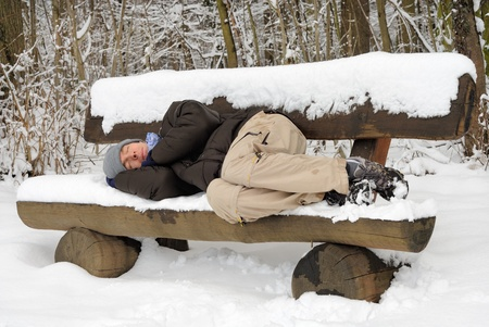 Photo for Exhausted young man sleeping on a snow-covered bench, ignoring the chill - Royalty Free Image
