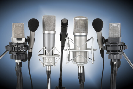 Photo for Studio shot of seven professional microphones in a row on blue background with spotlight - Royalty Free Image