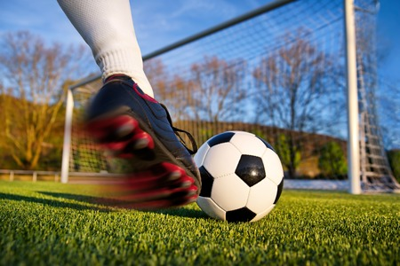 Photo pour Football or soccer shot with a neutral design ball being kicked, with motion blur on the foot and natural background - image libre de droit