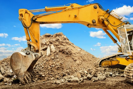 Foto de Yellow excavator and a heap of dirt, in the background a nice blue sky with white clouds - Imagen libre de derechos