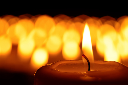 Photo for Candle in front of many defocused candleflames creating a spiritual atmosphere and in remembrance of loved ones - Royalty Free Image