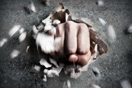Foto de a wall is broken through by a fist - Imagen libre de derechos