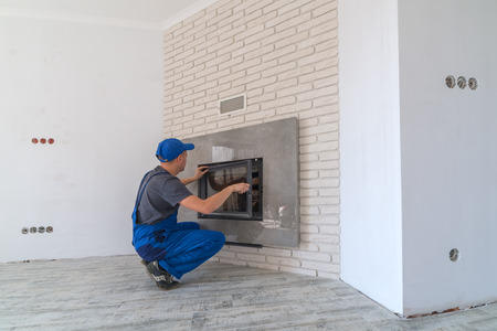 Photo pour Fireplace installing in white brick wall - image libre de droit