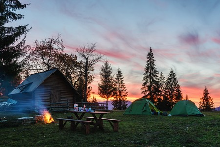 Photo pour Three tents lighted from the inside by a flashlight against the backdrop of an incredible sunset sky. Amazing evening landscape. Tourism concept - image libre de droit